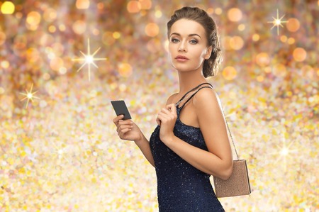 48853970 - people, luxury, holidays and finance concept - beautiful woman in evening dress with vip card and handbag over golden lights background