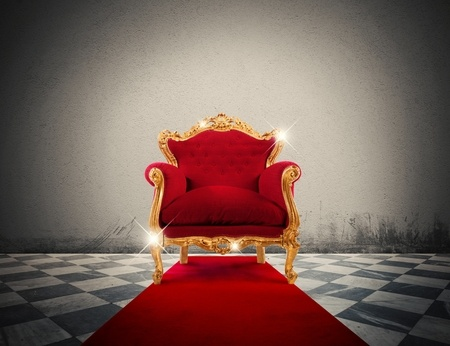 45342172 - sparkling golden armchair in a red carpet