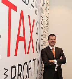 Photo of Arnold Waal next to a Tax tag cloud